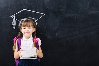 Menina do aluno com livros no chapéu mestre
