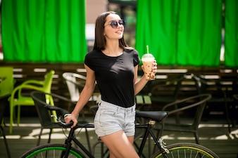 Menina em uma bicicleta bebendo café