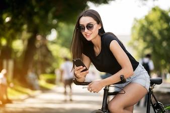 Menina em uma bicicleta com telefone