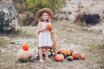 Menina encantadora em um chapéu de palha, cadeira de vime, abóboras, outono