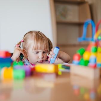 Menina fofa pequena brincando com marcador