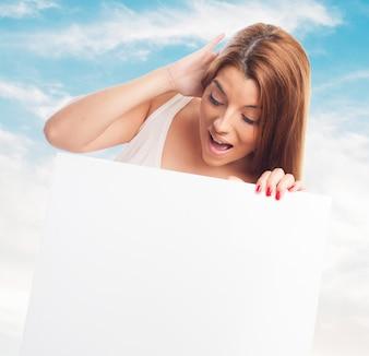 Menina lindo com placa em branco sobre o céu azul