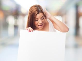 Menina morena com placa em branco rosto espantado segurando