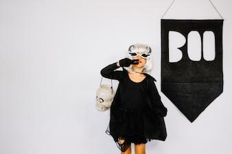 Menina no traje de Halloween mostrando o sinal da vitória