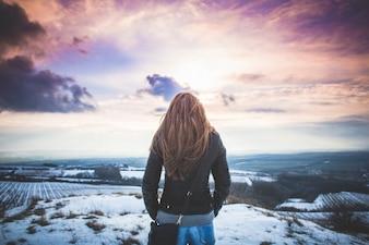 Menina observando a paisagem de inverno