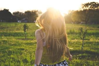 Menina que anda através do campo