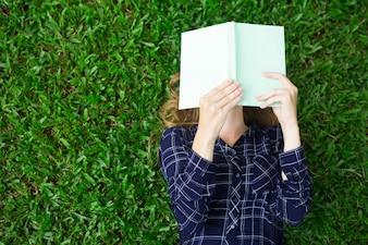 Menina que encontra-se no livro da grama e da leitura