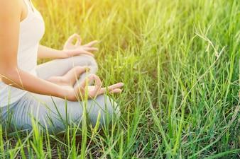 Menina que faz a ioga que senta-se no campo