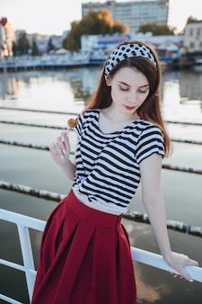 Menina que levanta a inclinação em uma cerca branca com fundo da água
