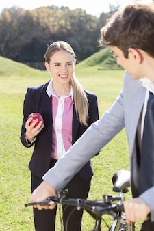 Menina que prende uma maçã e sorrindo para o seu parceiro