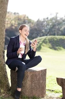 Menina que ri com seu celular