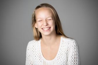 Menina que sorri com os olhos fechados