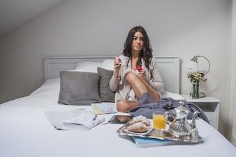 Menina que tem o pequeno almoço na cama