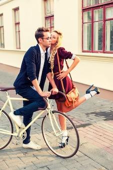 Menina romântica beijando seu namorado na bicicleta