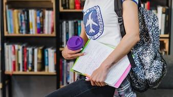 Menina segurando livro carregando mochila
