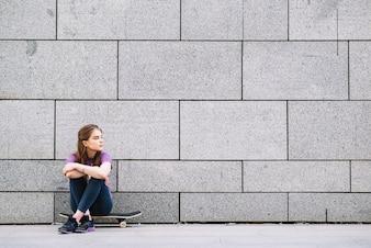 Menina sentada em um skate contra uma parede de tijolos