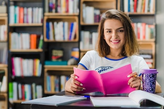 Menina sentada na mesa segurando o caderno