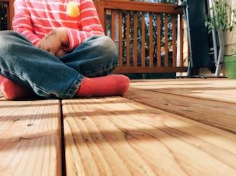 Menina sentada no chão de madeira