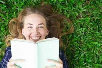 Menina sorridente deitada no livro de grama e de leitura