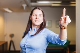 Menina sorridente tocando o ar com o dedo