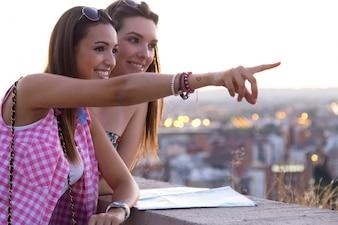 Meninas bonitas que olham as vistas na cidade.