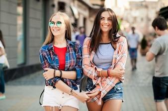 Meninas novas que andam mãos segurando