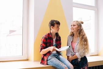 Meninas sentadas com livro didático