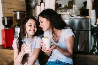 Meninas, sentando, café, segurando, copos