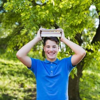Menino adolescente segurando livros em sua cabeça
