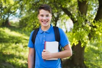 Menino adolescente sorridente com cadernos