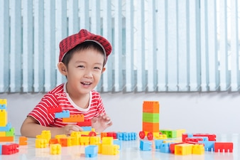 Menino bonito brincando com tijolos plásticos coloridos na mesa no quarto das crianças