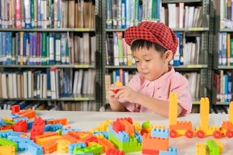 Menino brincando com blocos de plástico na escola da sala da biblioteca