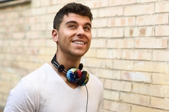 Menino com um grande sorriso e fones de ouvido ao redor do pescoço