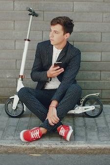 Menino elegante usando seu telefone móvel