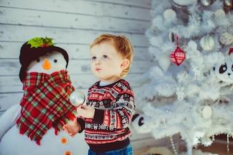 Menino em camisola de lã fica antes da árvore de natal branco