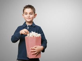 Menino feliz comendo pipoca