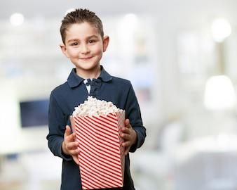 Menino feliz, segurando um balde de pipoca