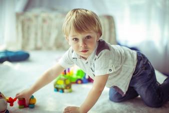 Menino fofo de camisa branca senta no chão e brinca com brinquedos