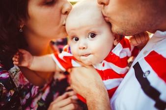 Menino parece engraçado enquanto os pais beijam sua cabeça