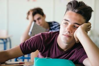 Menino sonolento na aula
