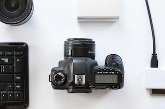 Mesa branca com uma câmera profissional e acessórios sobre ela
