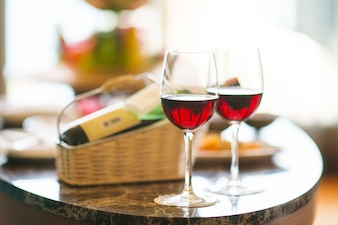 Mesa com duas taças de vinho e fundo desfocado