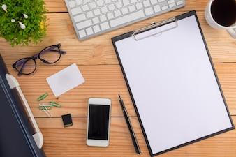 Mesa de escritório com caneta, teclado no caderno, xícara de café e flor. Vista superior com espaço de cópia (foco seletivo).
