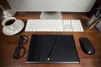 Mesa de escritório com computador, telefone celular e pertences
