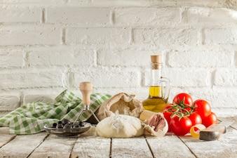 Mesa de madeira com massa e ingredientes frescos