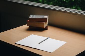 Mesa de trabalho com caderno e livros