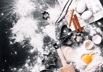 Mesa preta cheia de farinha e ovos com decorações do Natal