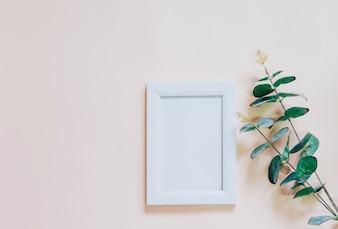 Mockup de quadro de foto em branco com planta verde em fundo amarelo, estilo simples e mínimo