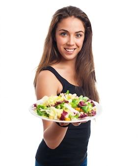 Modelo magro agradável oferece uma salada
