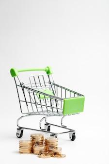 MOEDAS pilha e carrinho de compras em um fundo branco